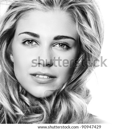 beautiful blond woman with long curly hair on white background touching her face - stock photo