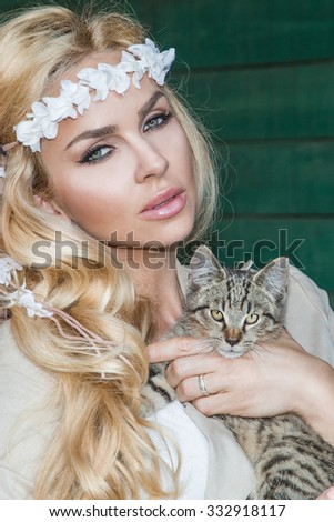 Beautiful blond woman with long hair pretty sexy eyes and mouth on the wild west with a sweet gray kitten on hands - stock photo