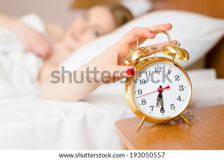 beautiful blond young woman blocking alarm clock off wake up time & looking at clock - stock photo