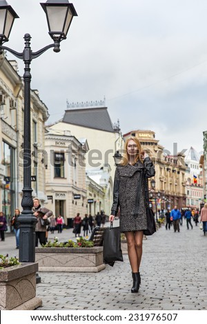 Beautiful blond young woman dressed in a coat walking down the street of the old town center - stock photo