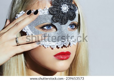 Beautiful Blond Young Woman in Carnival Mask.Masquerade. Beauty Girl with red lips. Manicure.Close-up portrait - stock photo