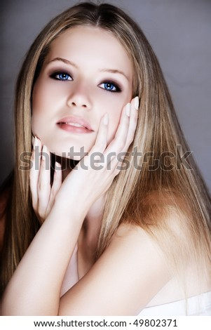 Beautiful blond young woman in her 20s with soft smile and hands around her face - stock photo