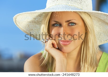 Beautiful blond young woman or girl in her twenties happy smiling wearing sun hat resting on her hand in sunshine on summer day with blue sky - stock photo