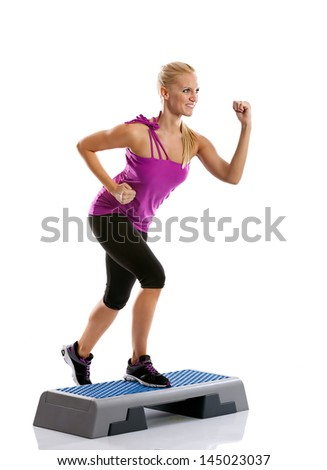 Beautiful blond young woman performing step aerobics exercise - stock photo
