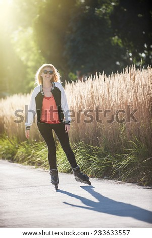 beautiful blond young woman practicing rollerblading in town - stock photo