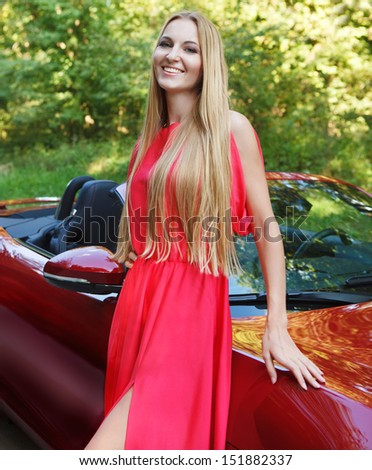 Beautiful blond young woman standing near a  sports car - stock photo