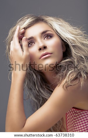 beautiful blond young woman with curly hair and natural make-up - stock photo