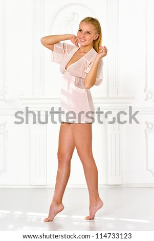 Beautiful blonde barefoot woman  in lingerie in white interior studio. - stock photo