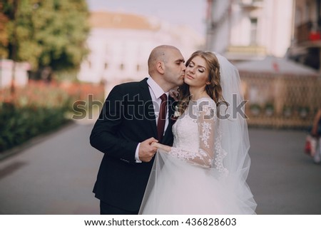 beautiful blonde bride enjoys her wedding day in the summer - stock photo
