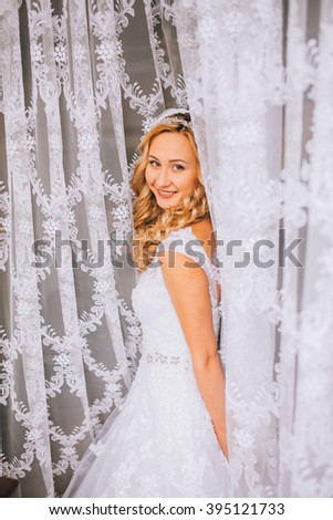 Beautiful blonde bride in wedding dress posing under curtain - stock photo