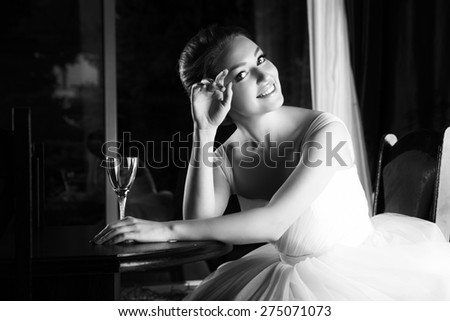 Beautiful blonde bride seats near table, is ready for a new bright life, inside interior. White Wedding dress. Pretty young woman love. Black and white photo. - stock photo