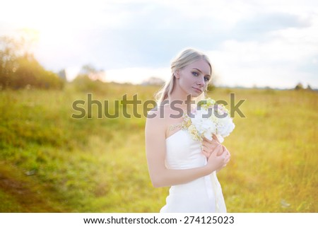 Beautiful blonde bride standing in a field on a background of a beautiful sunset and looking at the camera and smiling. Beautiful bride. Wedding Day. Beautiful Happy woman - stock photo