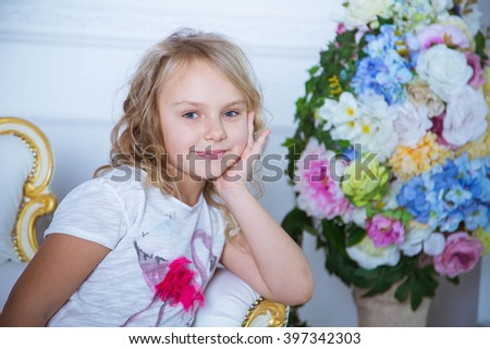 Beautiful blonde caucasian girl sitting on a white chair. Girl smiling and looking in camera - stock photo