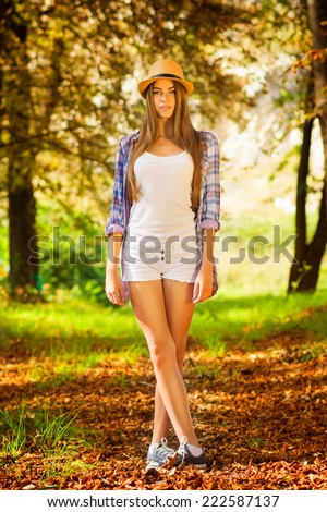 Beautiful blonde Caucasian teenage girl with hat in outdoors in park in autumn standing looking at camera wearing white shorts and checkered shirt. Full body length vertical image.  - stock photo