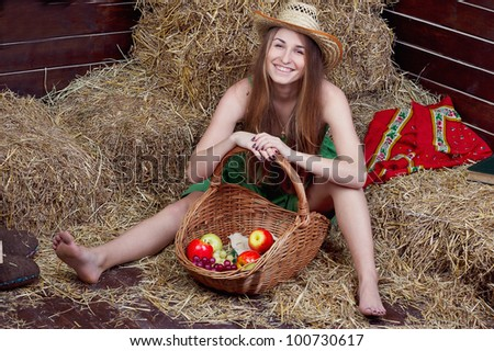 beautiful blonde country girl posing on yellow hay with basket of apples - stock photo