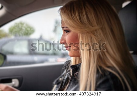 Beautiful blonde crying while driving - stock photo