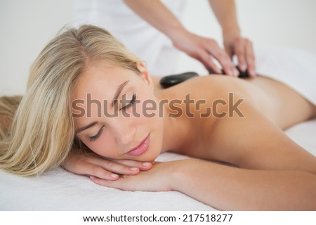 Beautiful blonde enjoying a hot stone massage at the health spa - stock photo