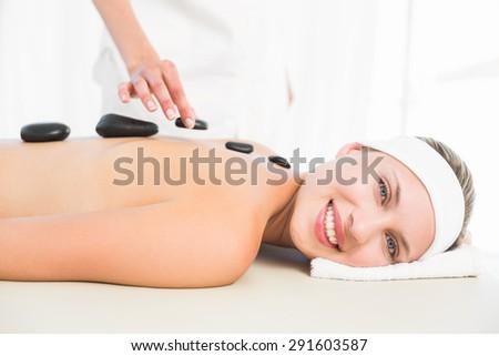 Beautiful blonde enjoying a hot stone massage at the health spa - stock photo