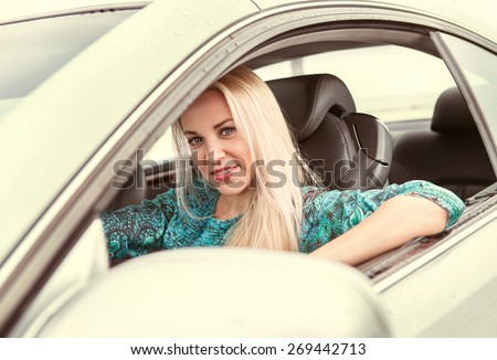 Beautiful blonde female behind the own car steering wheel - stock photo