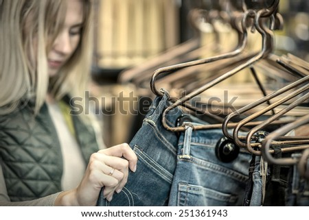 Beautiful blonde female looking jeans in the boutique - stock photo