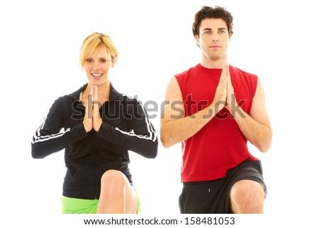 beautiful blonde female yoga instructor training young man. - stock photo