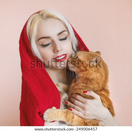 Beautiful blonde girl and her ginger cat. Color toned image. Soft focus on eyes. - stock photo
