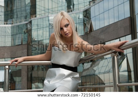 beautiful blonde girl dressed in a futuristic style against the backdrop of modern buildings - stock photo