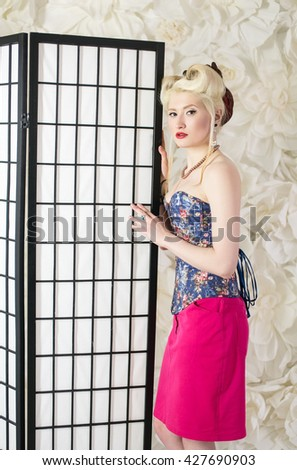 Beautiful blonde girl, dressed in the style of pin up posing near the white wall and the screen for changing clothes, fashion, beauty - stock photo
