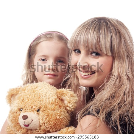 beautiful blonde girl embracing little child with her toy - stock photo