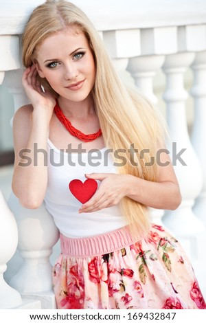 Beautiful blonde girl holding heart in hand  - stock photo