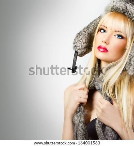 Beautiful blonde girl in fur hat on grey background - stock photo