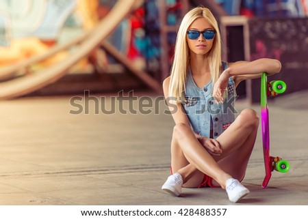 Beautiful blonde girl in glasses is leaning on her skateboard and looking at camera while sitting on the ground in skate park - stock photo