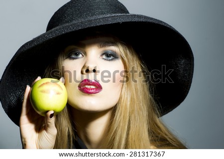 Beautiful blonde girl in retro black hat with bright make up looking forward holding fresh green apple standing on gray background copyspace, horizontal picture - stock photo