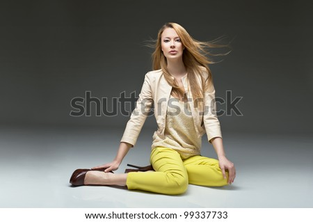 beautiful blonde girl in stylish clothes, yellow pants leather jacket and high heels. Fashion model posing at studio - stock photo