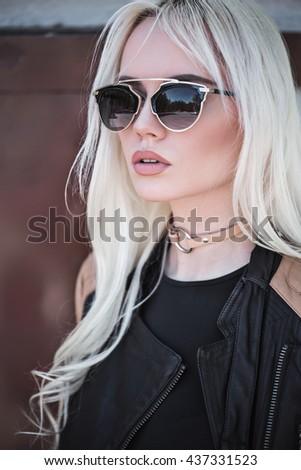 Beautiful blonde girl in sunglasses outside - stock photo