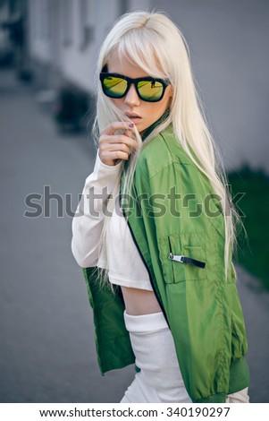 Beautiful blonde girl in sunglassses outdoors - stock photo