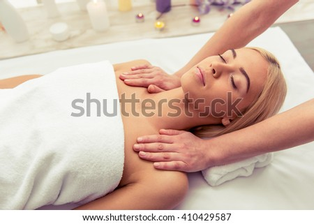 Beautiful blonde girl is lying with closed eyes at spa while a massage therapist is massaging her head - stock photo