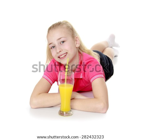Beautiful blonde girl lies on the floor in front of her and there was a glass of orange juice- isolated on white background - stock photo