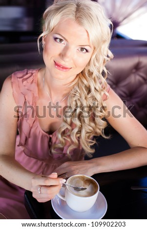Beautiful blonde girl posing sitting in a cafe on the table cappuccino. - stock photo