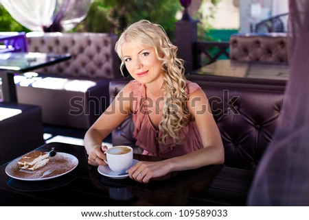 Beautiful blonde girl posing sitting in a cafe on the table cappuccino and tiramisu cake. - stock photo