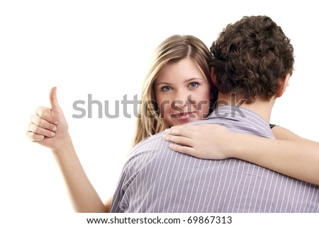 beautiful blonde girl showing the thumb up looking out of her boyfriend's back - stock photo