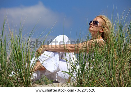 Beautiful blonde girl sitting on a sand in dunes - stock photo