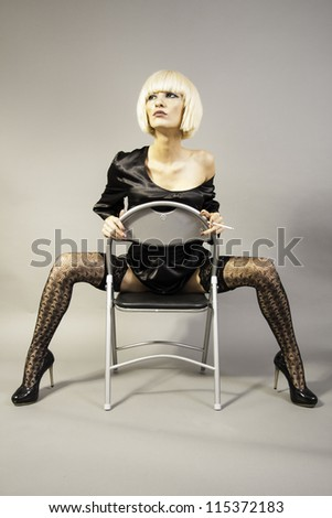Beautiful blonde girl sitting on the chair - stock photo