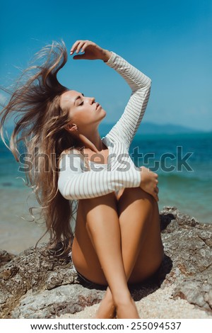 beautiful blonde girl with long hair posing on the beach in a white t-shirt and closed eyes - stock photo