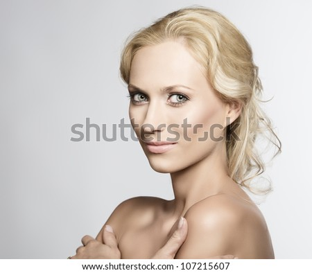 beautiful blonde girl with nudes shoulders and natural makeup, she is turned of three quarters at right with crossed arms, looks in to the lens and smiles - stock photo