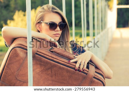 Beautiful blonde girl with sunglasses holding a suitcase and dreaming about traveling the world. - stock photo