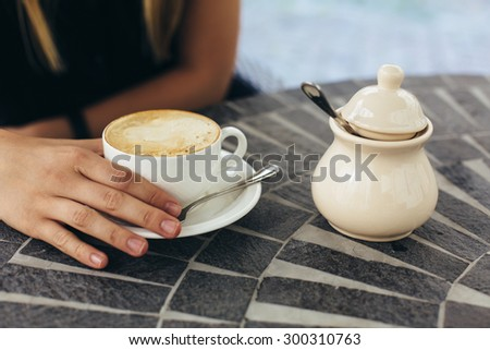 beautiful blonde happy young caucasian girl with long gorgeous hair is drinking coffee in cafe  coffee shop alone during sunny summer day morning on vacation lifestyle shot - stock photo
