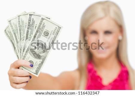 Beautiful blonde holding 100 dollars banknotes against white background - stock photo