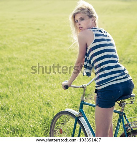 beautiful blonde in a field on a bicycle - stock photo