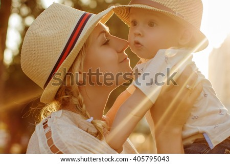 Beautiful blonde in a hat mother kissing her son at sunset in the summer, close-up - stock photo